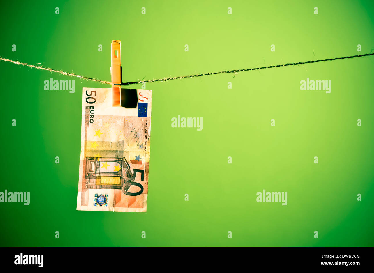 Fifty Euro banknote hanging on a clothesline, green background. - Stock Image