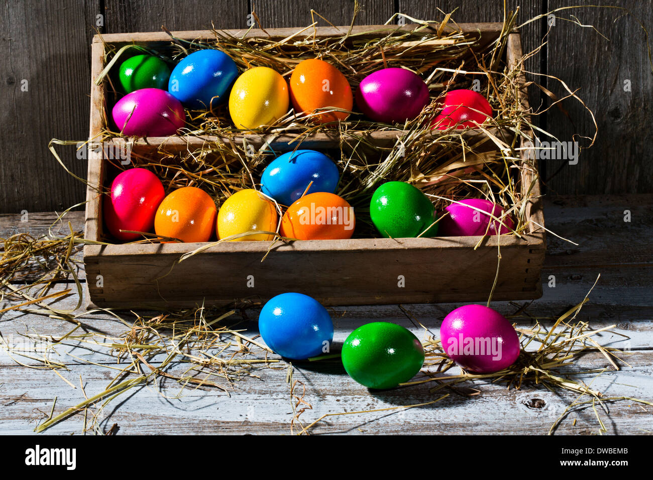 Wooden box of shiny coloured Easter eggs on wooden ground - Stock Image