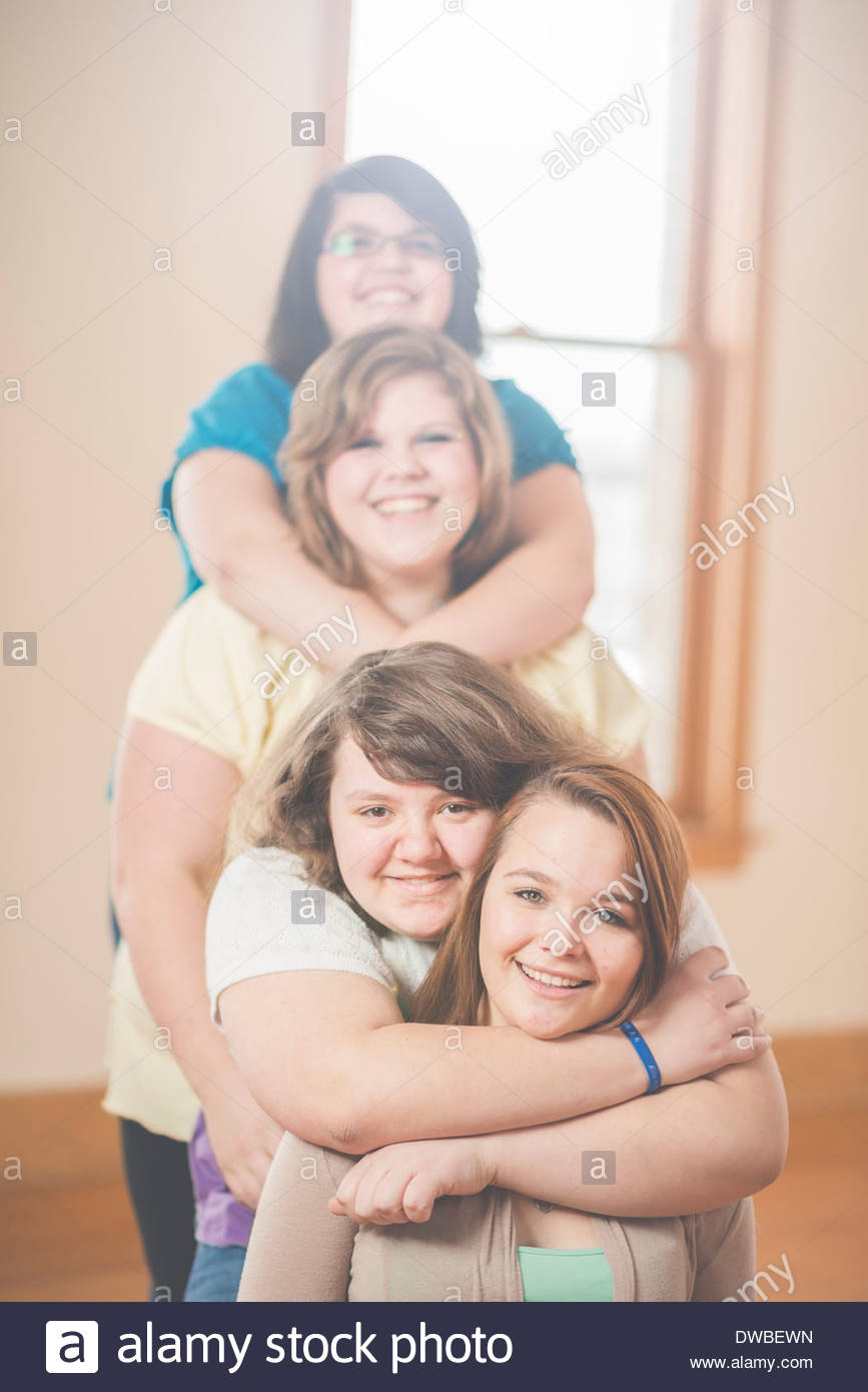 Portrait of four sisters hugging in a row - Stock Image
