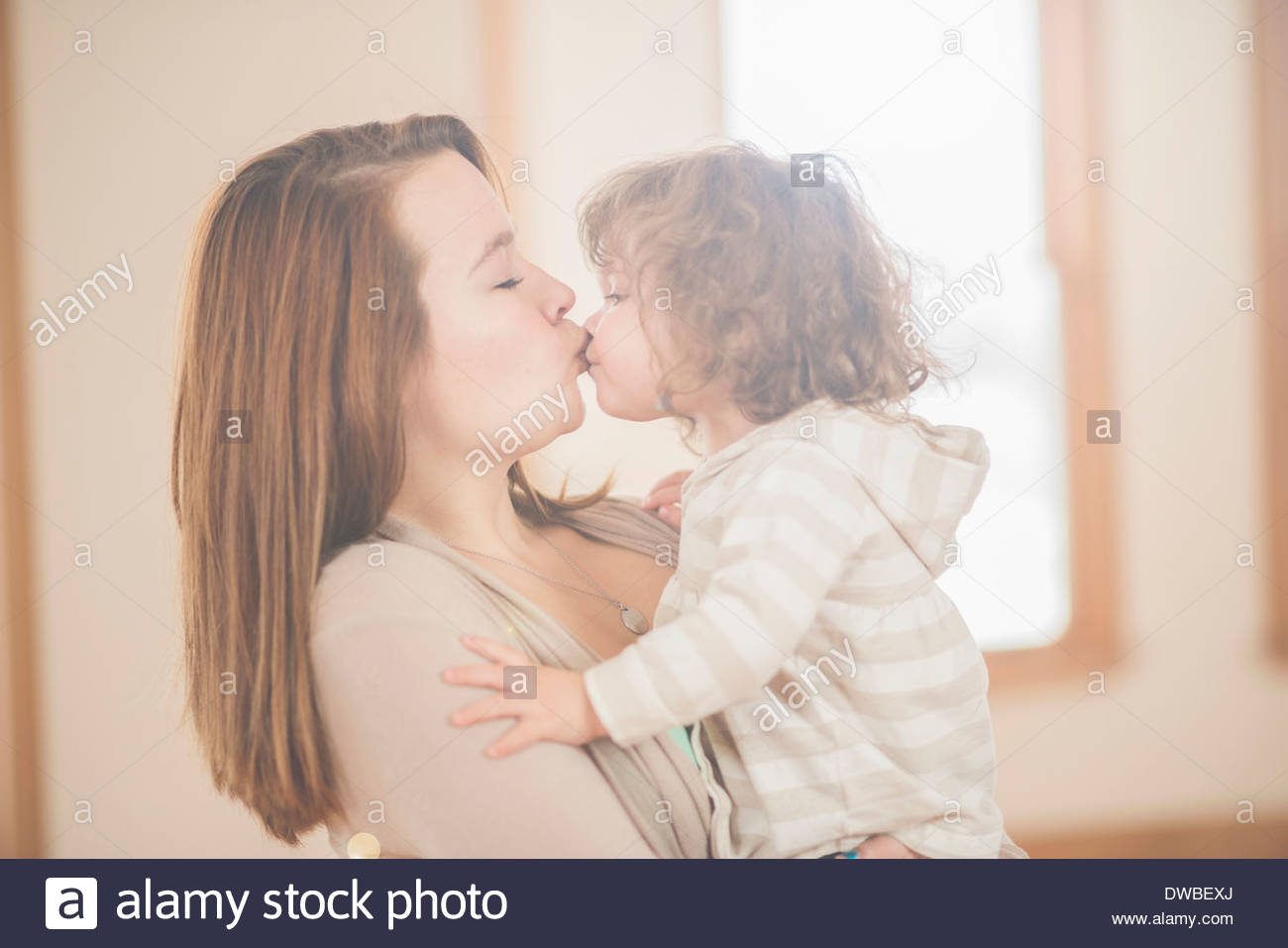 Female toddler and adoring teenage aunt - Stock Image