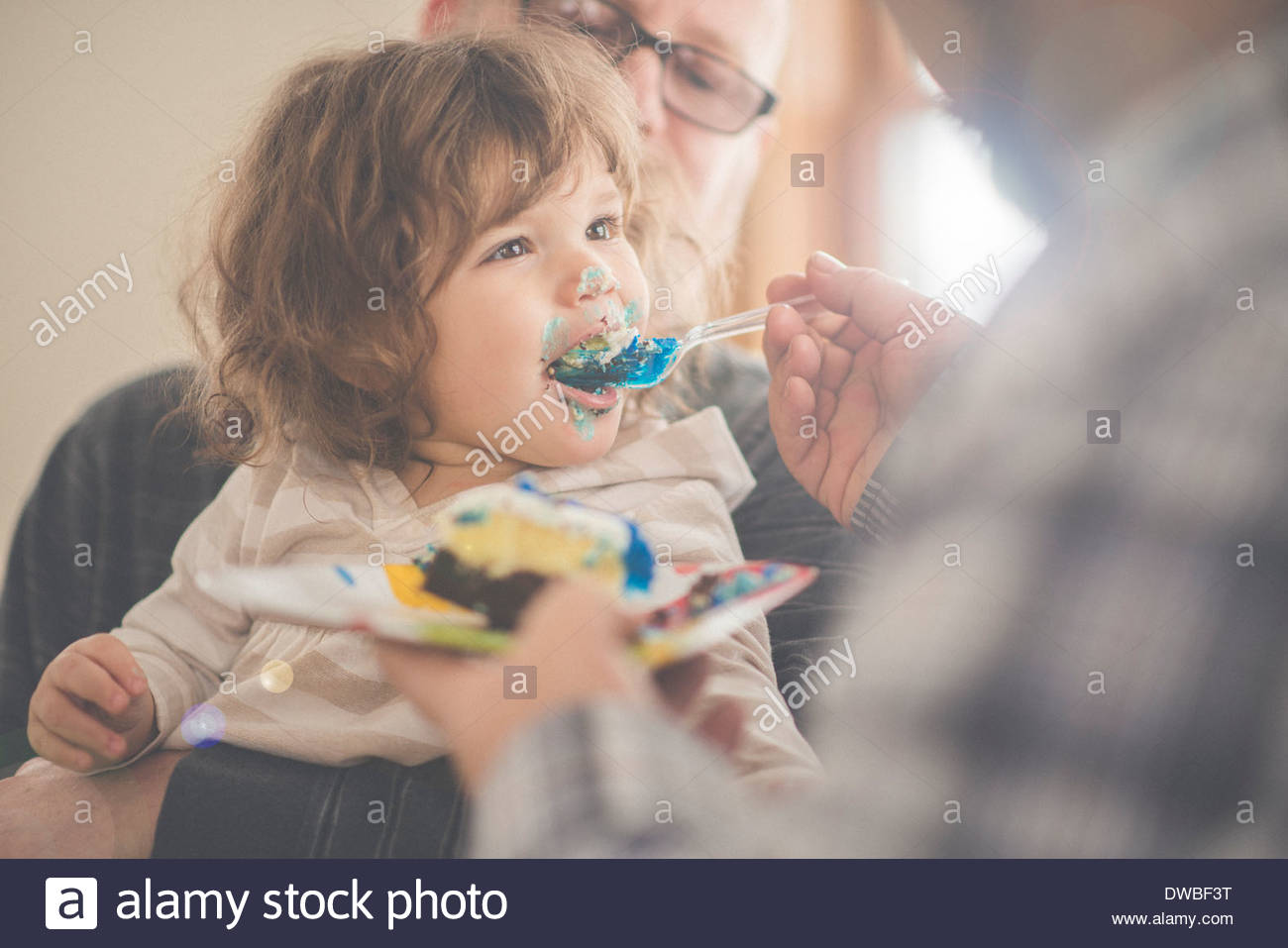 Female toddler being fed with birthday cake - Stock Image