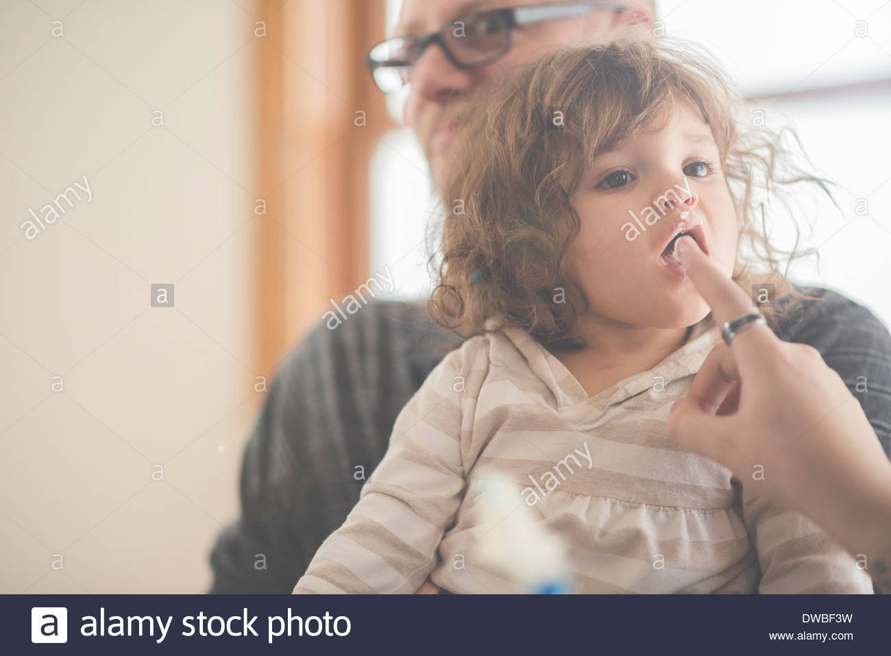 Female toddler licking grandmothers finger - Stock Image