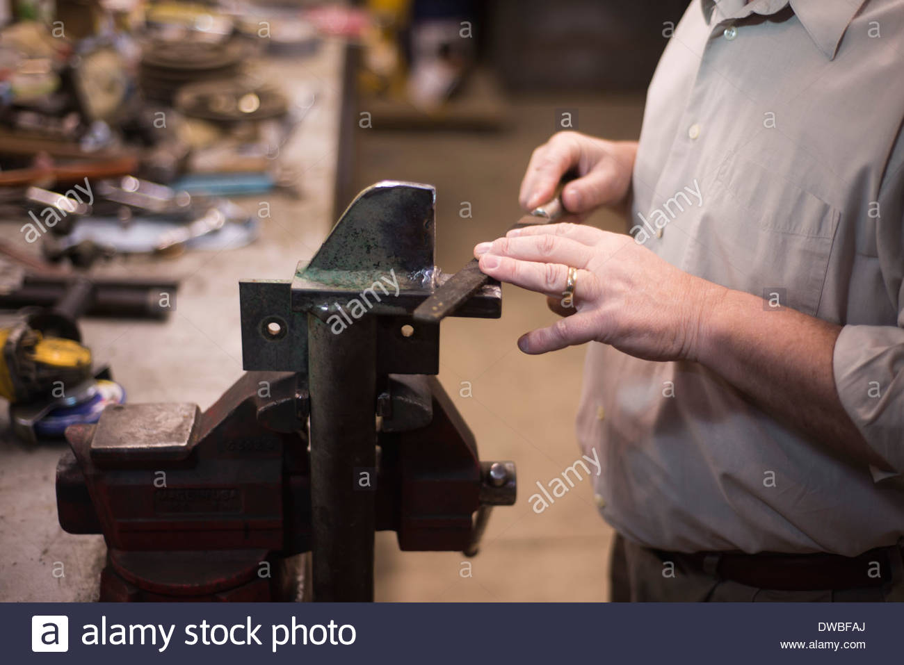 Mid section of man in workshop with clamp - Stock Image