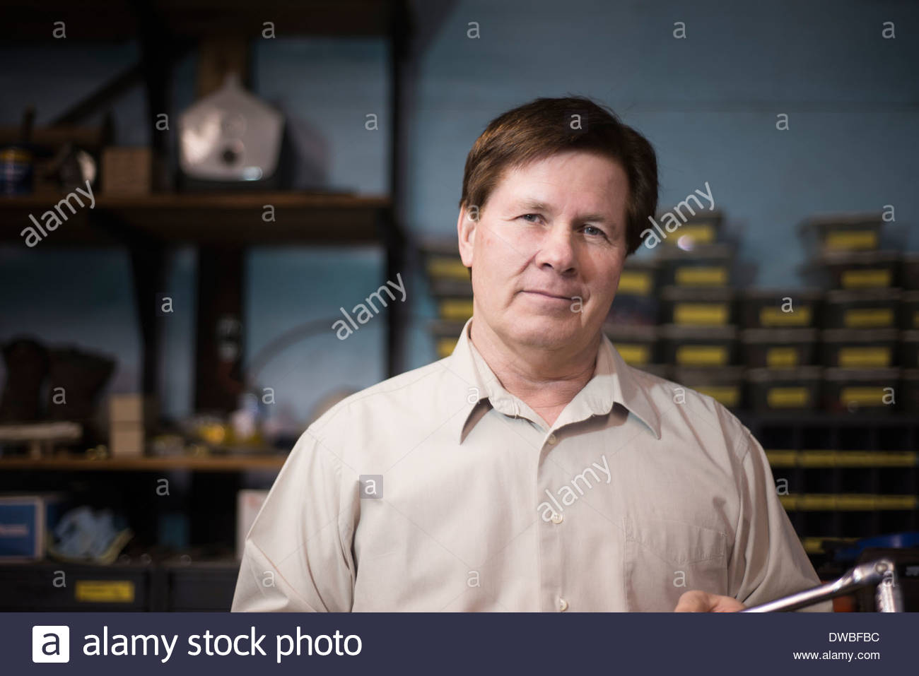 Senior man standing in workshop - Stock Image