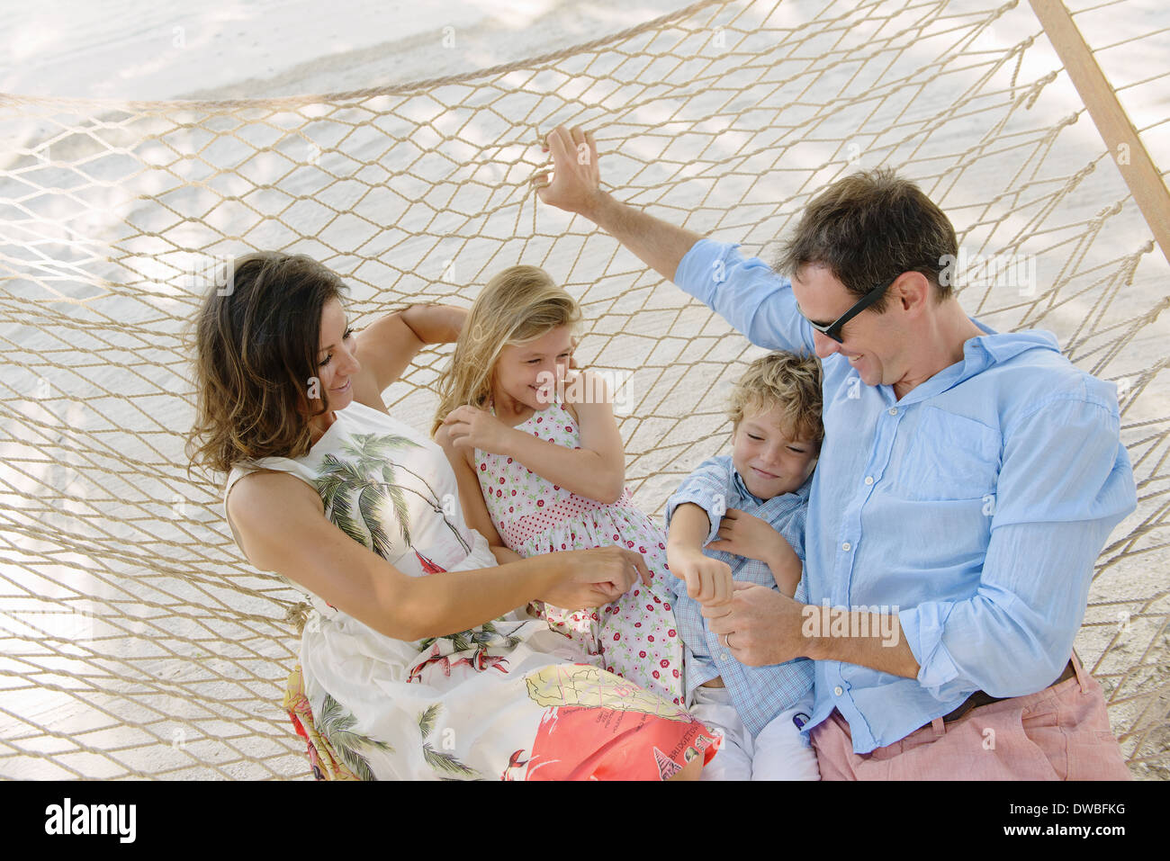 Family relaxing in beach hammock, Providenciales, Turks and Caicos Islands, Caribbean - Stock Image