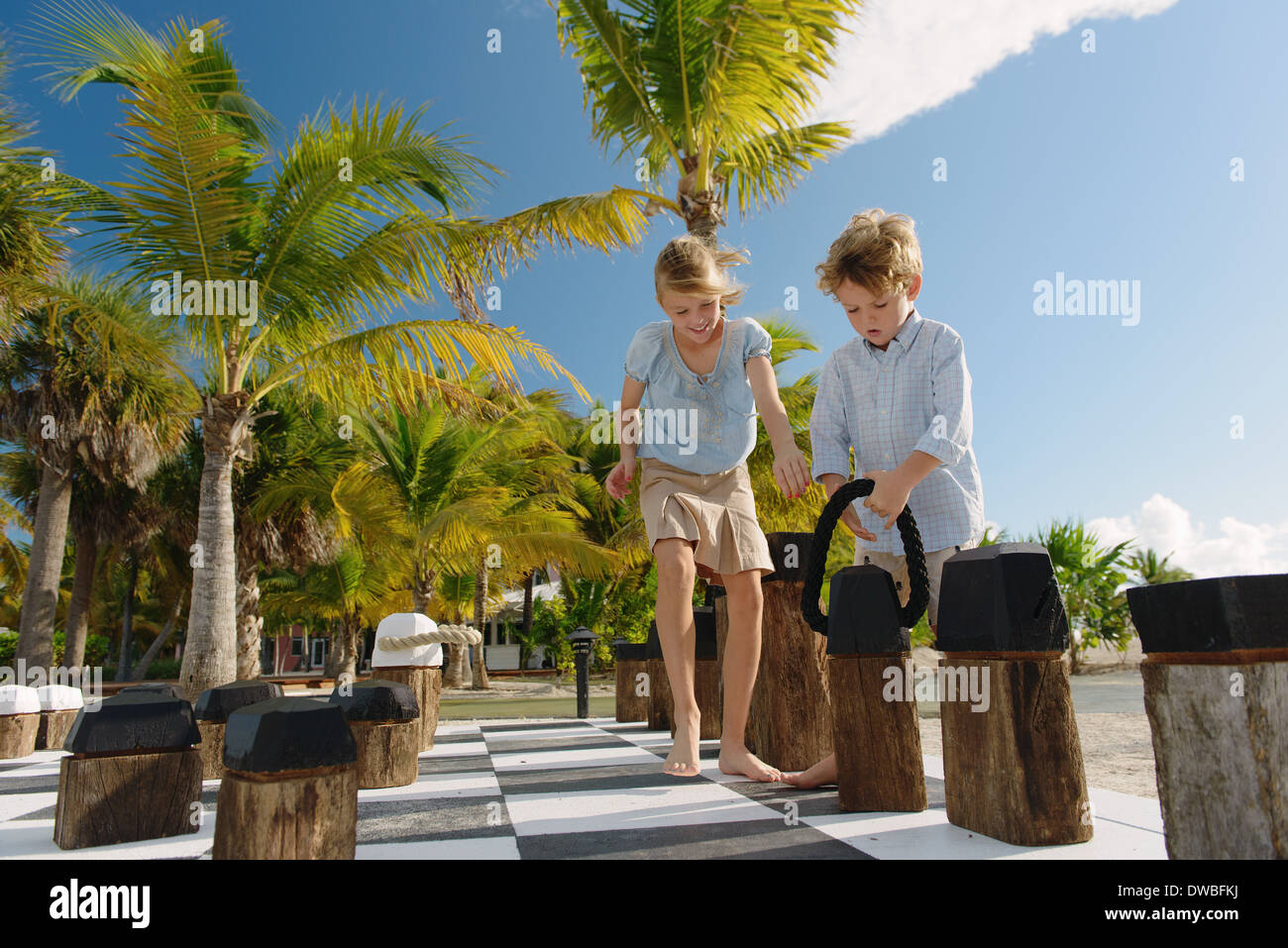 Brother and sister playing giant chess, Providenciales, Turks and Caicos Islands, Caribbean - Stock Image