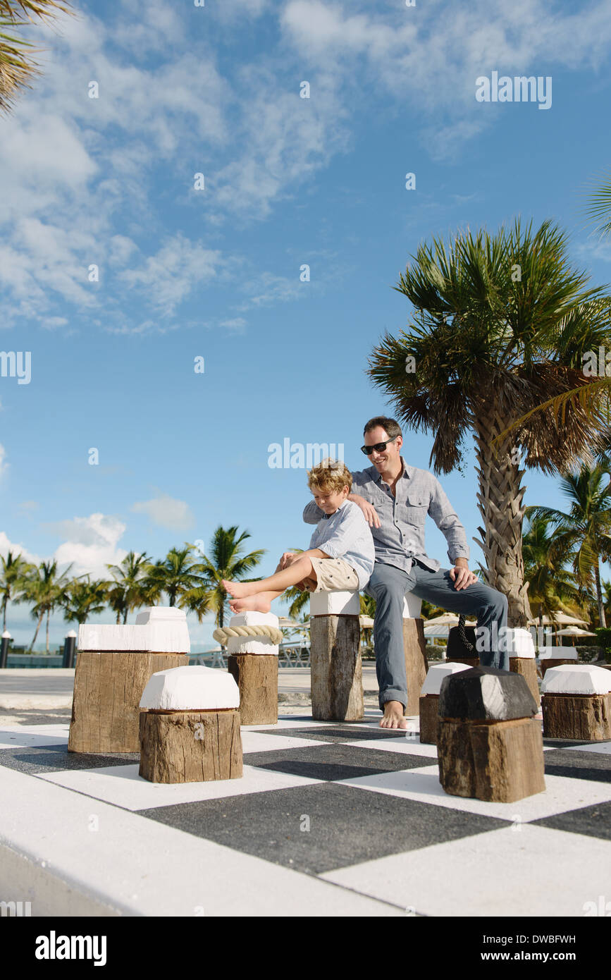 Father and son sitting on giant chess set, Providenciales, Turks and Caicos Islands, Caribbean - Stock Image