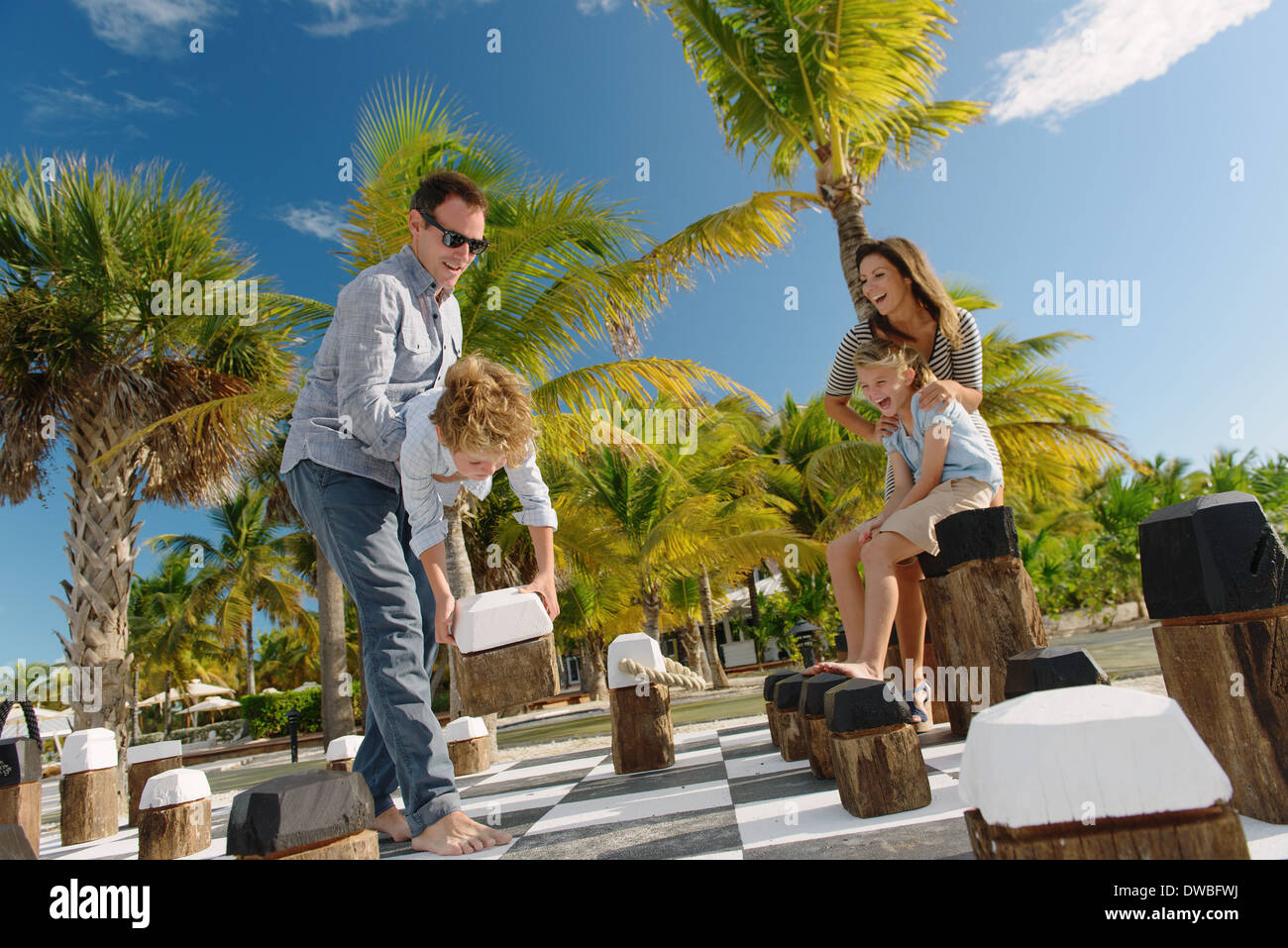 Family playing giant chess, Providenciales, Turks and Caicos Islands, Caribbean - Stock Image