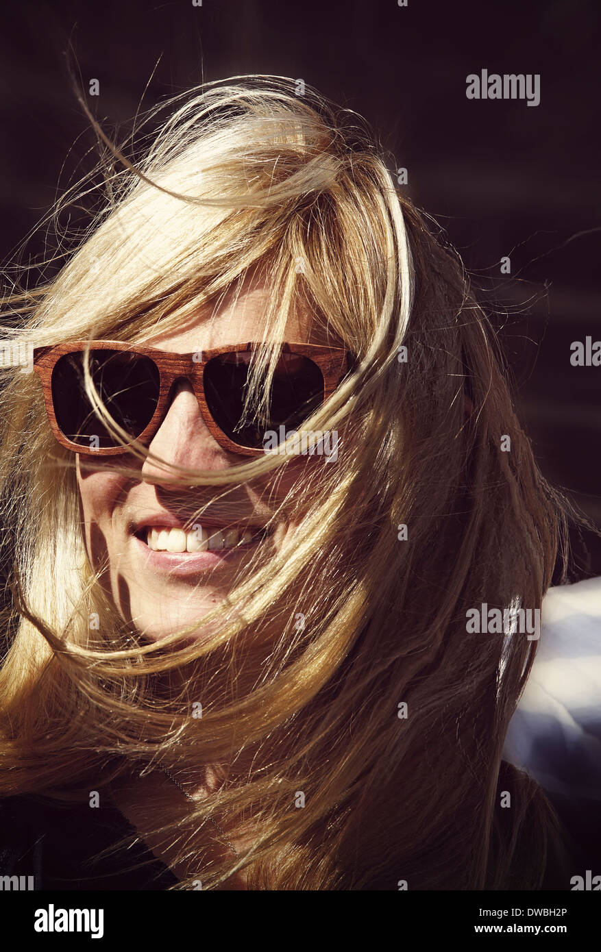 Smiling young woman with blowing hairs wearing sunglasses - Stock Image