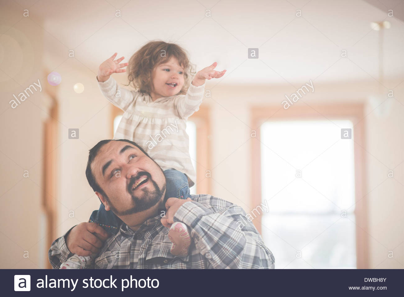 Toddler daughter up on fathers shoulders - Stock Image