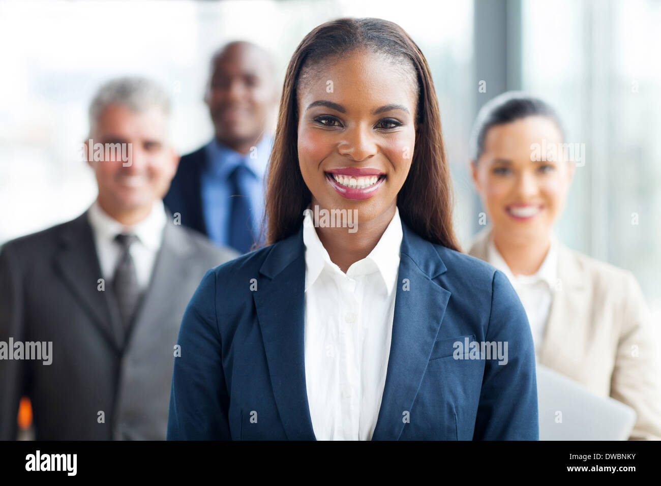 pretty African American businesswoman standing in front of co-workers - Stock Image