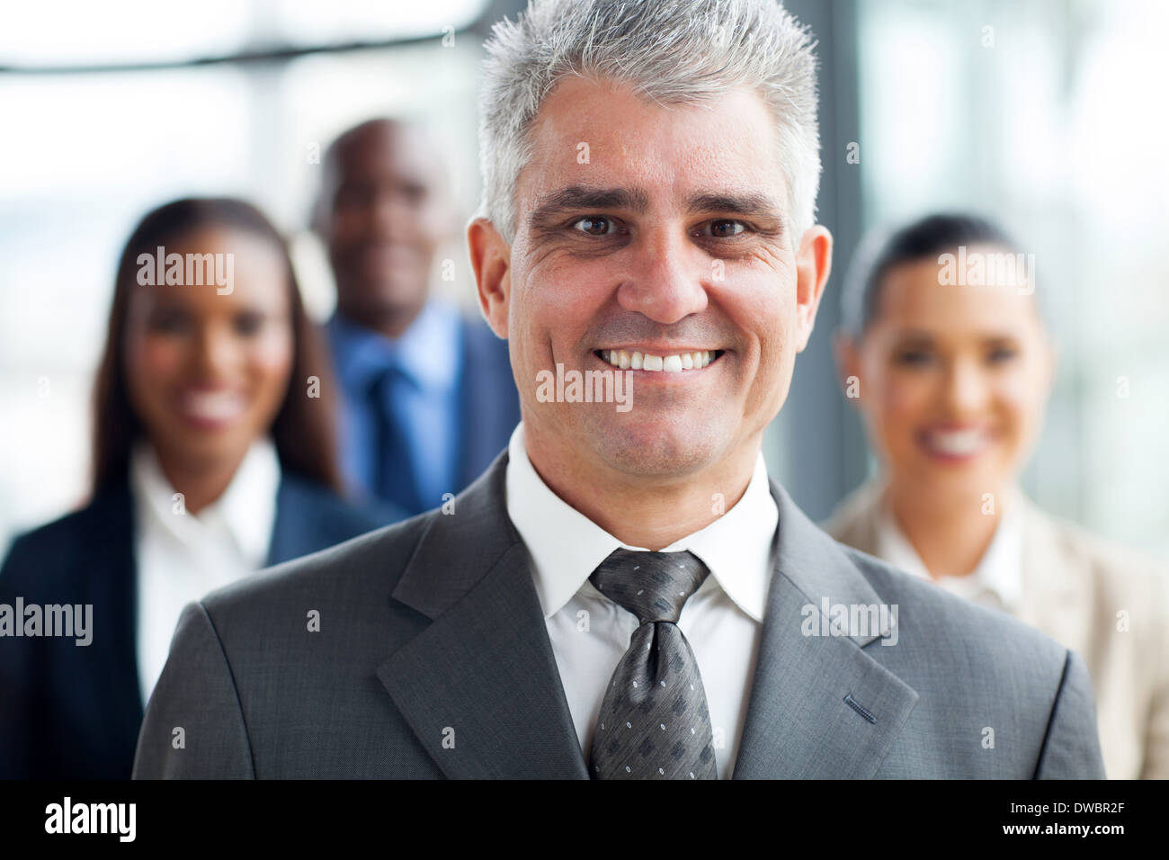 handsome senior businessman standing with co-workers on background - Stock Image