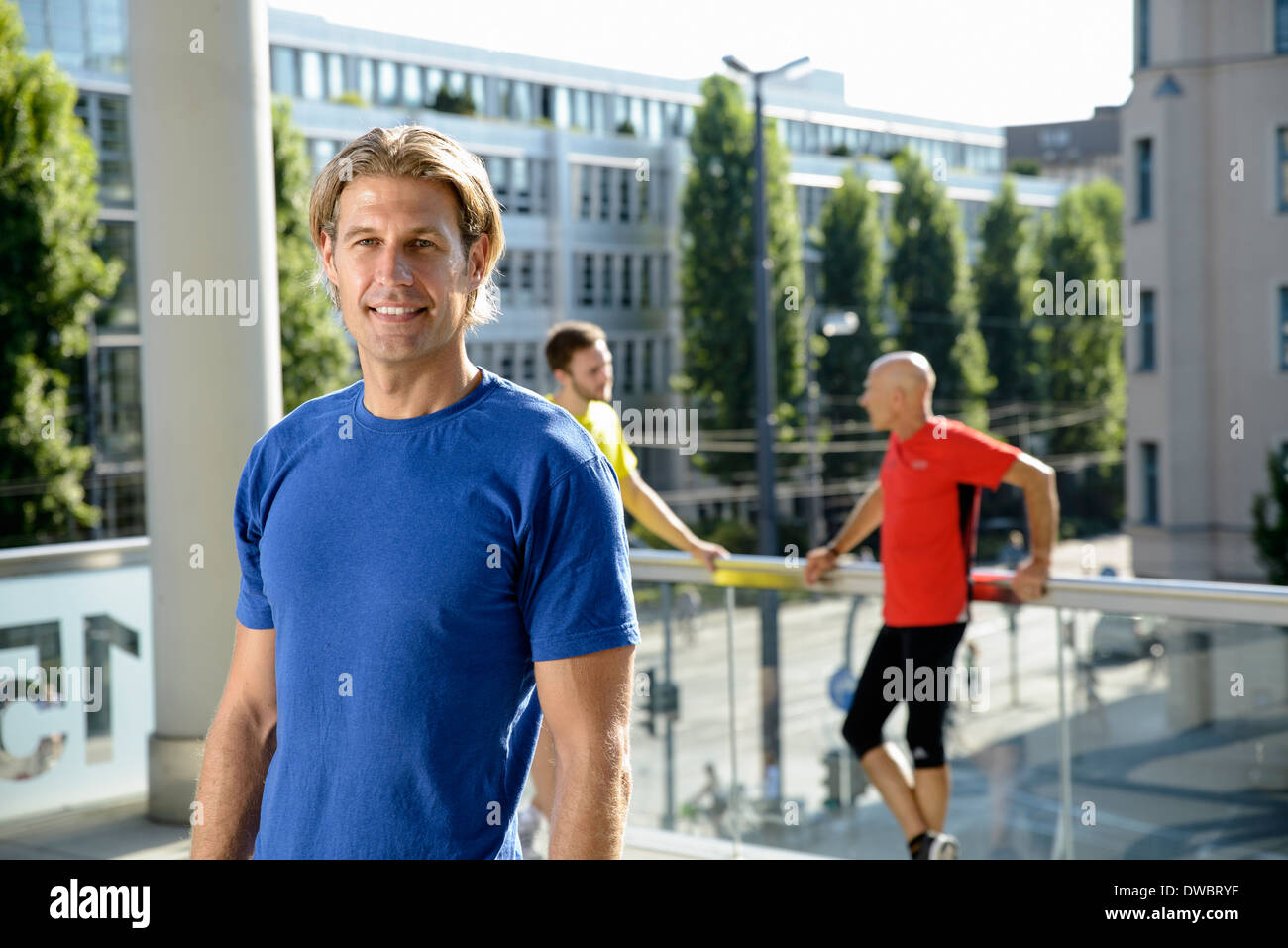 Mid adult male trainer and class taking a break on city rooftop - Stock Image
