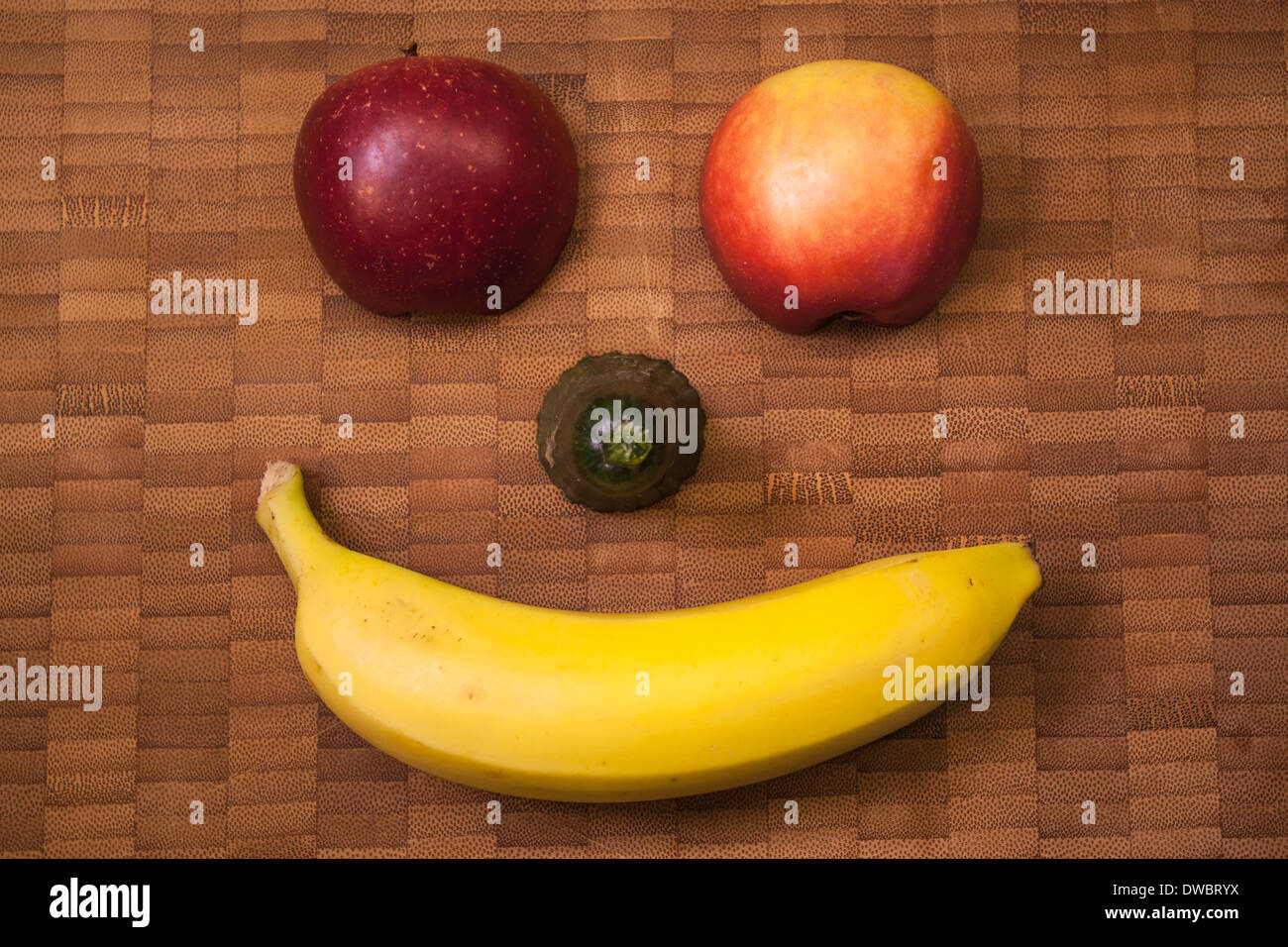Banana On Table Funny fruit face with banana, cucumber, and apple on wooden table, close up