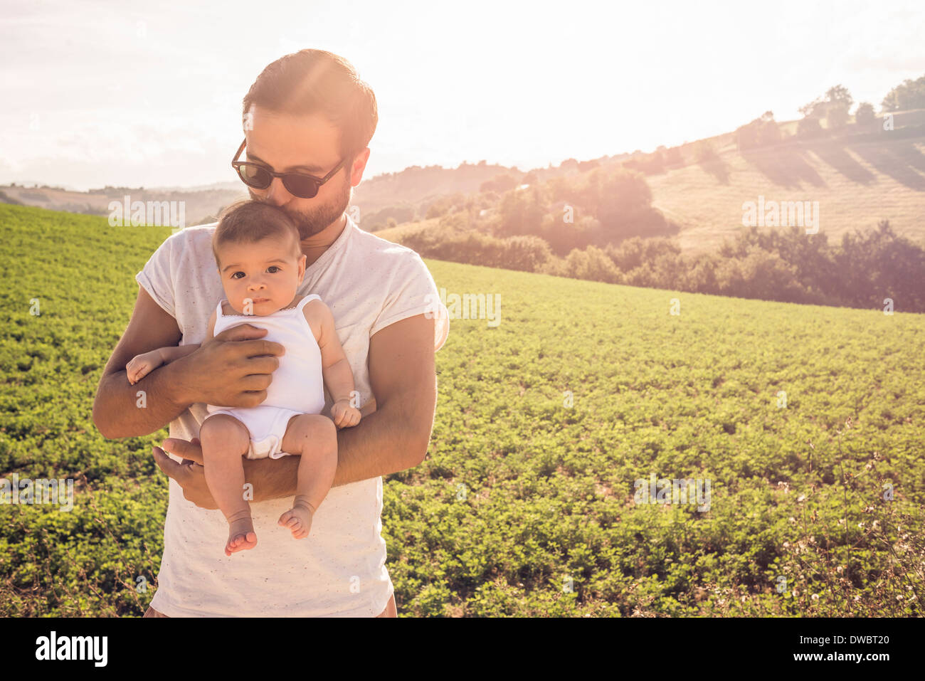 Portrait of proud father holding up baby daughter - Stock Image