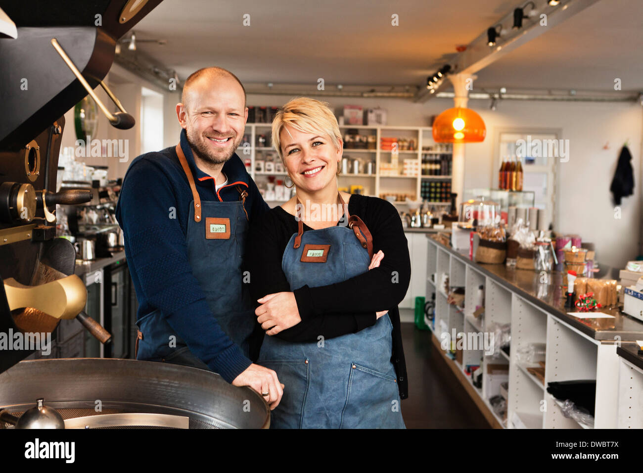 Mature couple in coffee shop kitchen - Stock Image