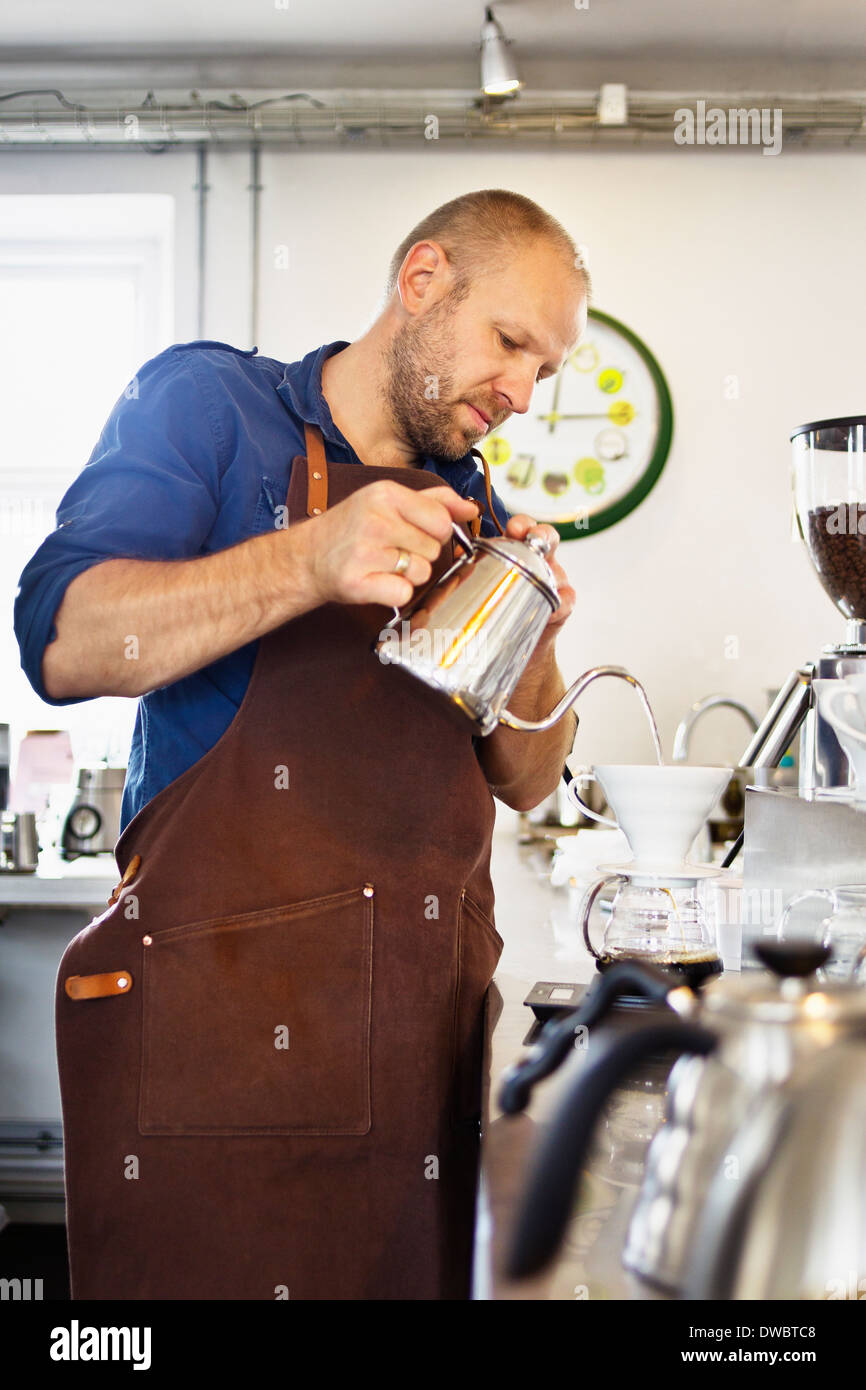 Male barista pouring boiling water into coffee filter - Stock Image
