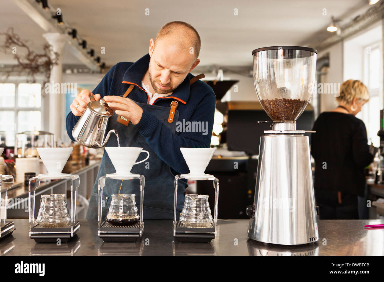 Barista pouring boiling water into coffee filters Stock Photo
