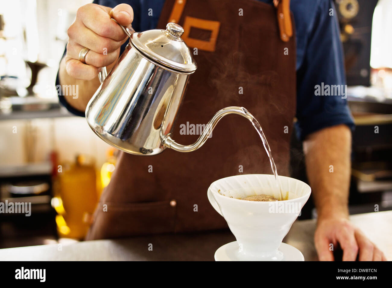 Close up of barista pouring boiling water into coffee filter - Stock Image