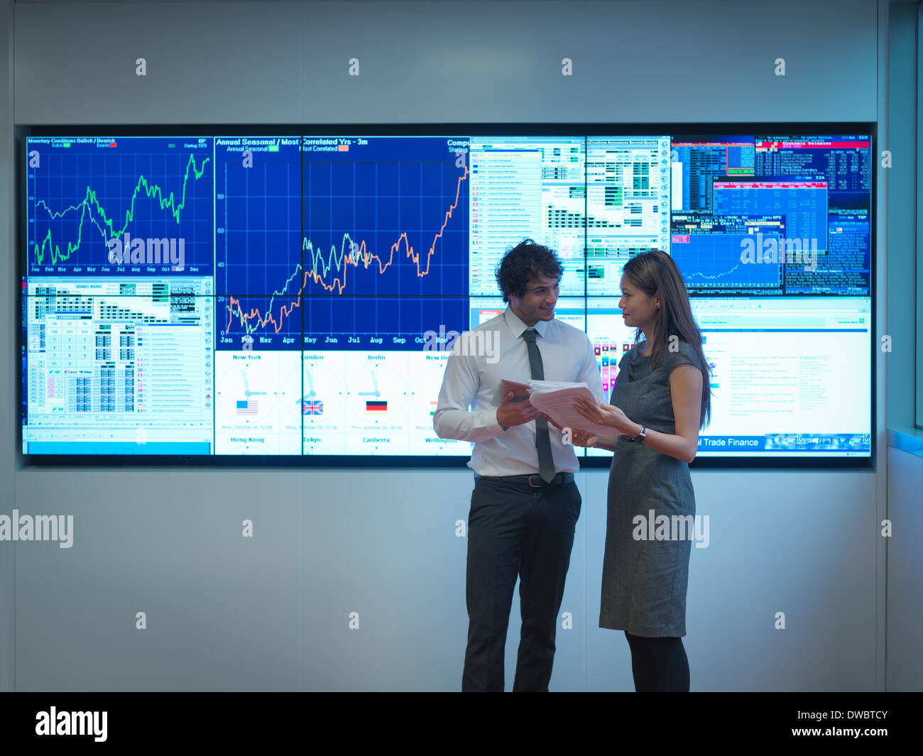 Business people meeting in front of graphical screens - Stock Image