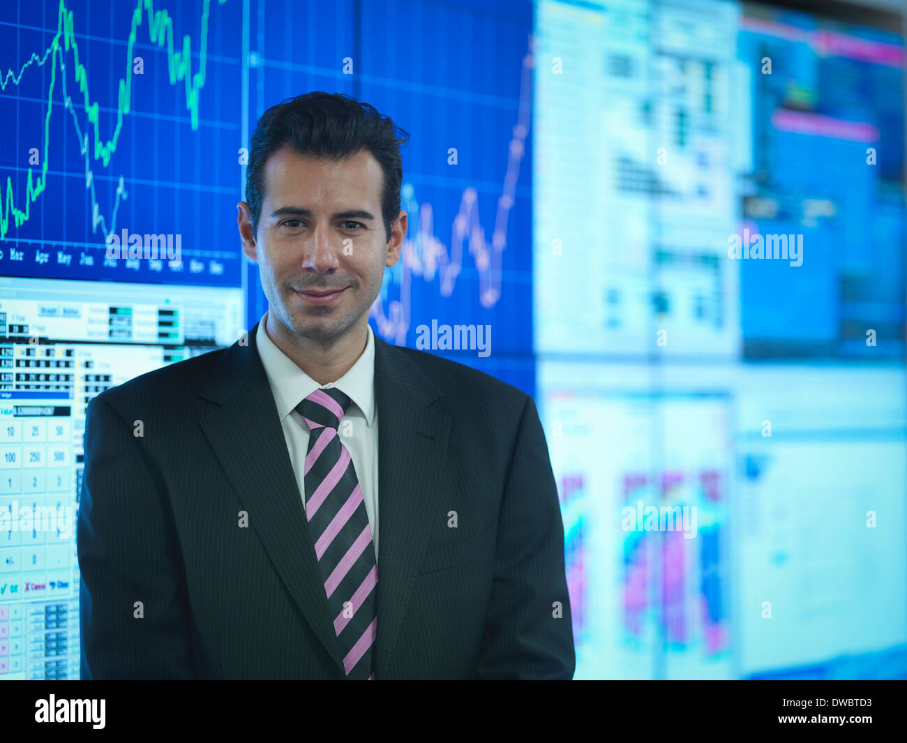 Portrait of businessman in front of presentation on graphical screens - Stock Image