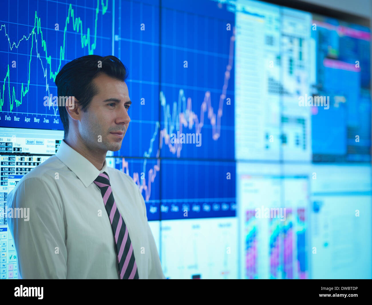 Businessman in front of presentation on graphical screens - Stock Image