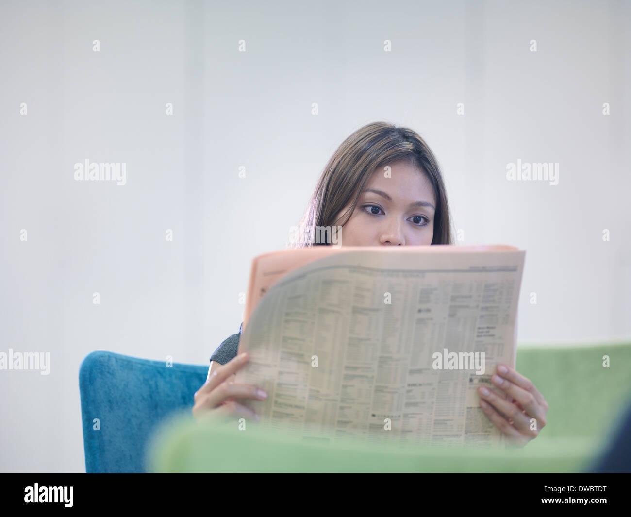 Businesswoman reading British newspaper - Stock Image