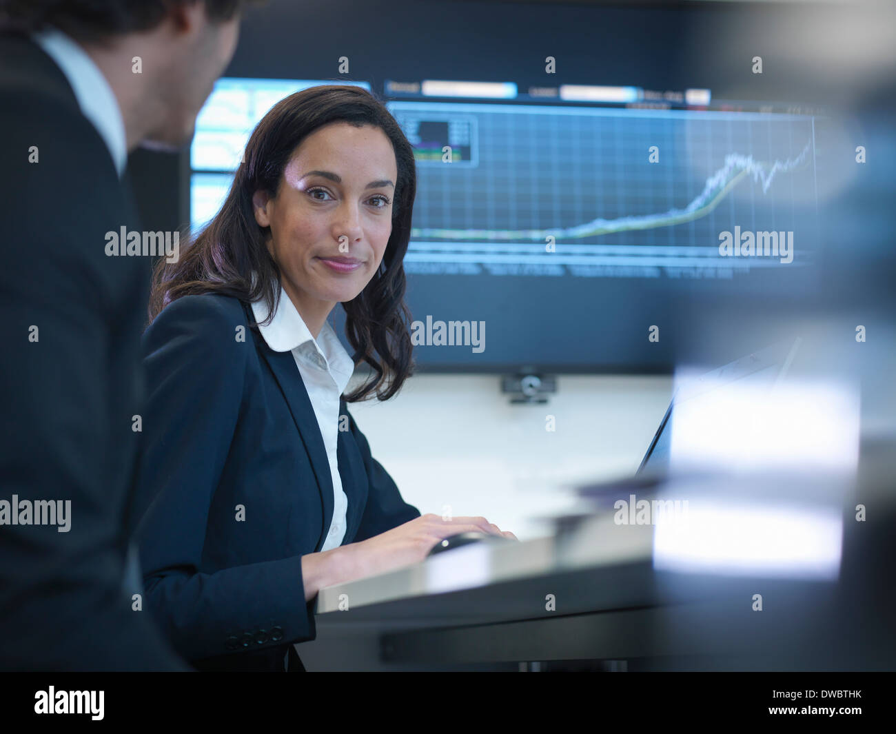 Portrait of businesswoman in meeting in front of screen in office - Stock Image