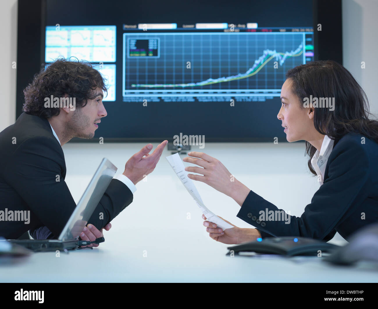 Business colleagues in meeting in front of screen in office - Stock Image