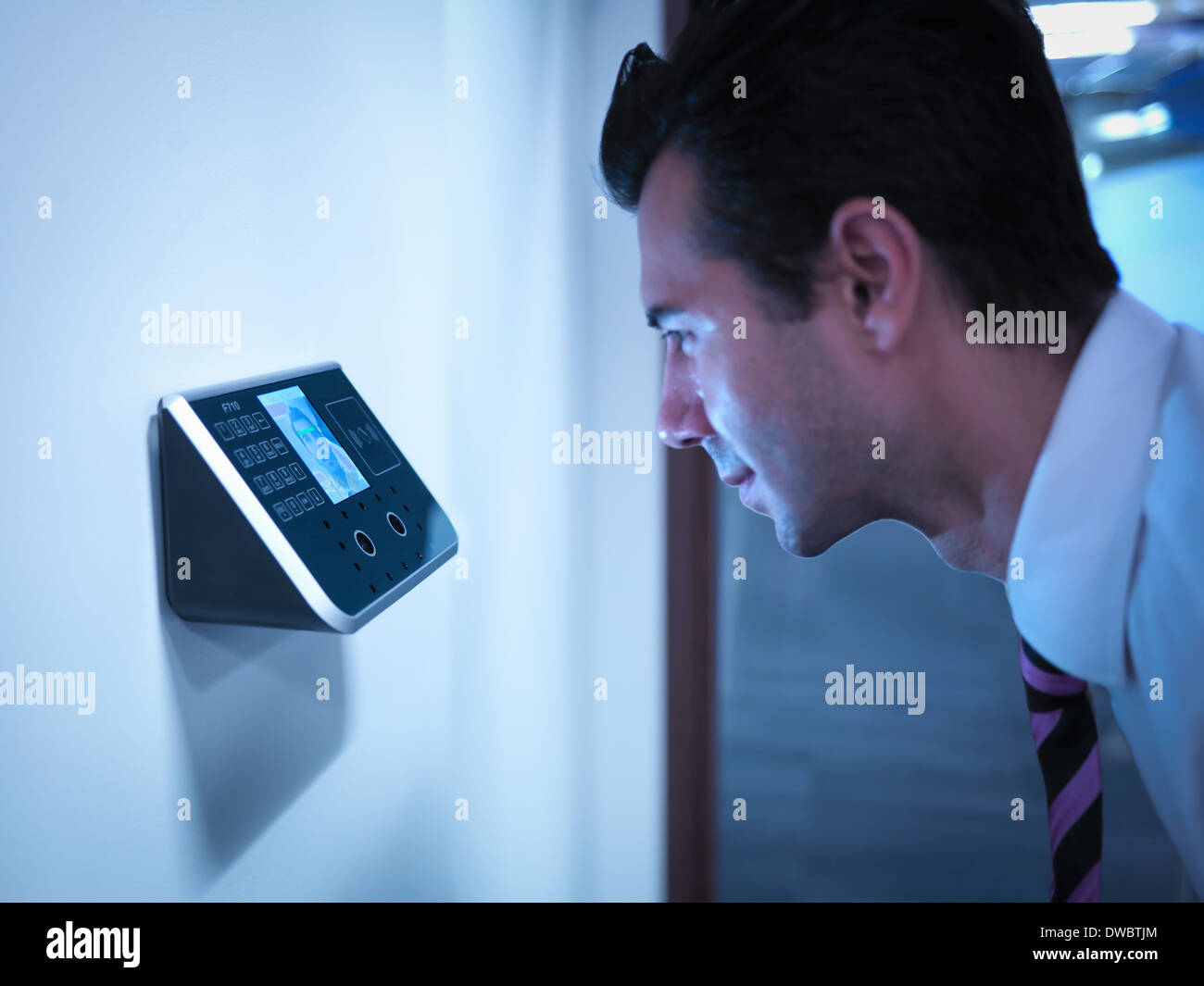 Businessman using face recognition system for office security - Stock Image