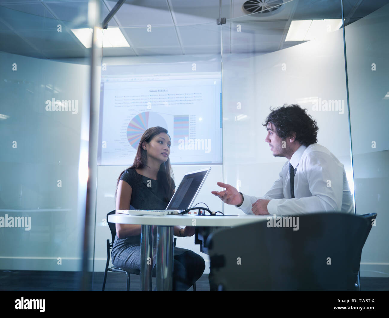 View through glass windows of meeting room of business colleagues in discussion - Stock Image