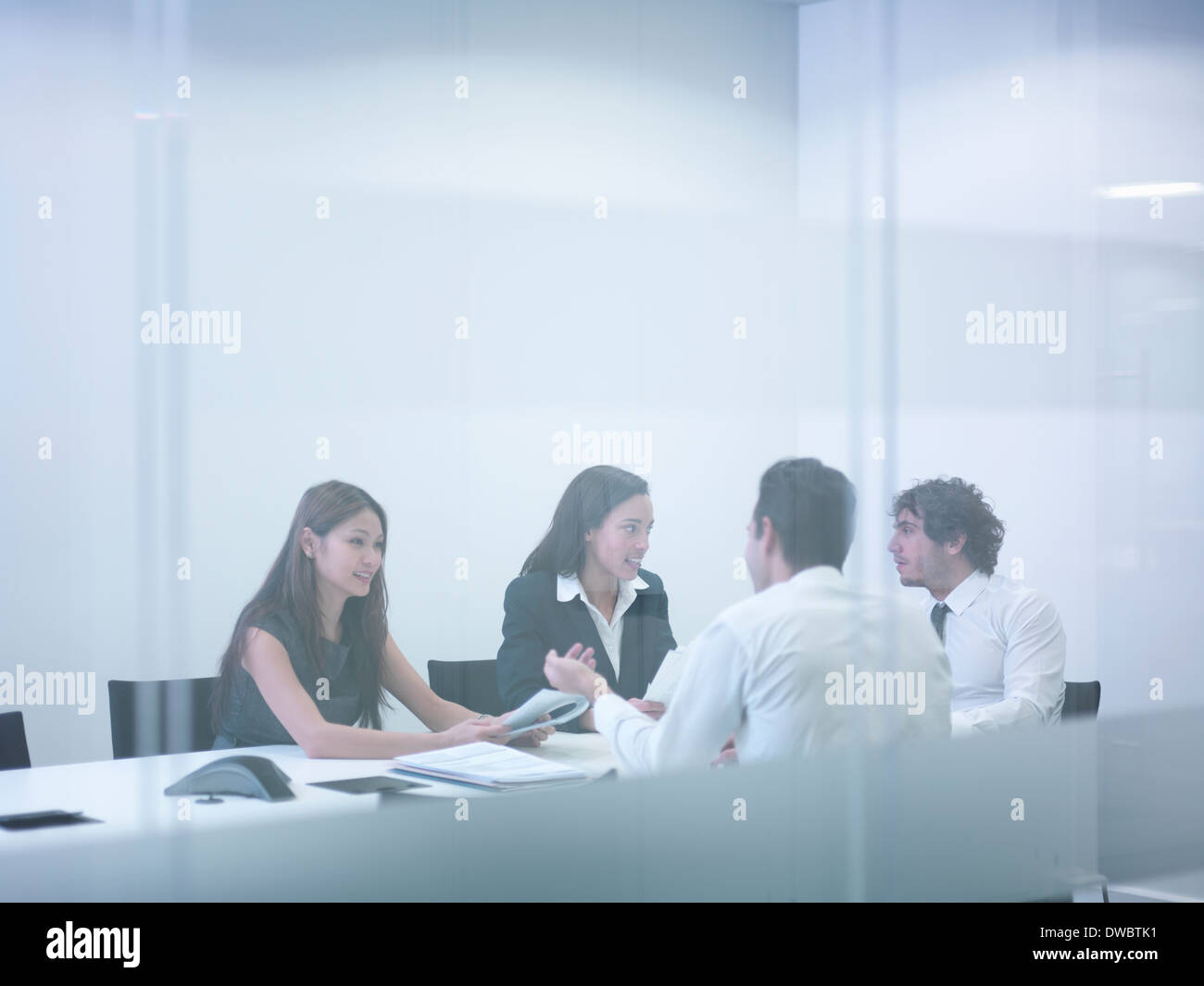 View through glass wall of business colleagues in meeting - Stock Image