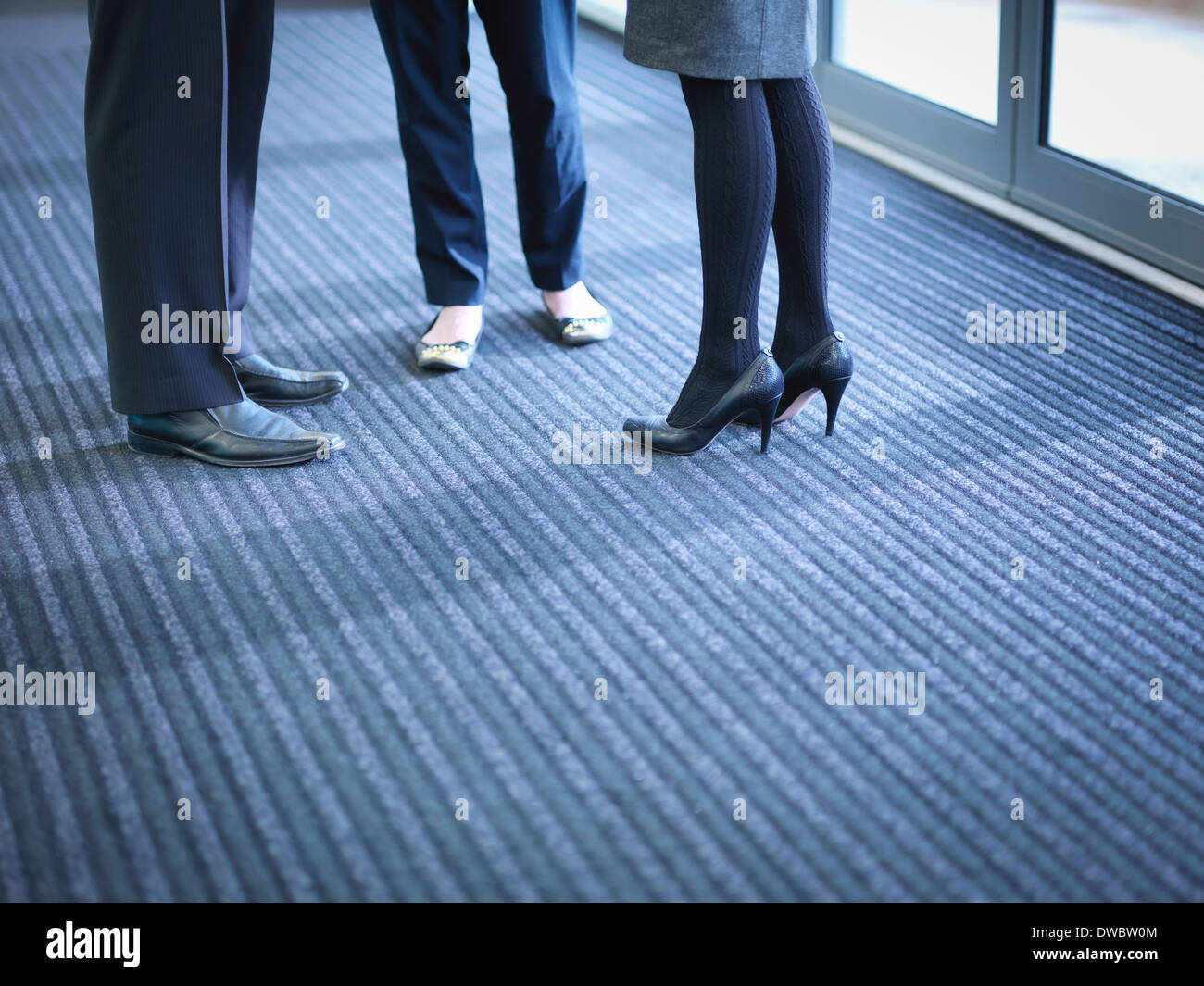 Business colleagues in meeting in office foyer, low section - Stock Image