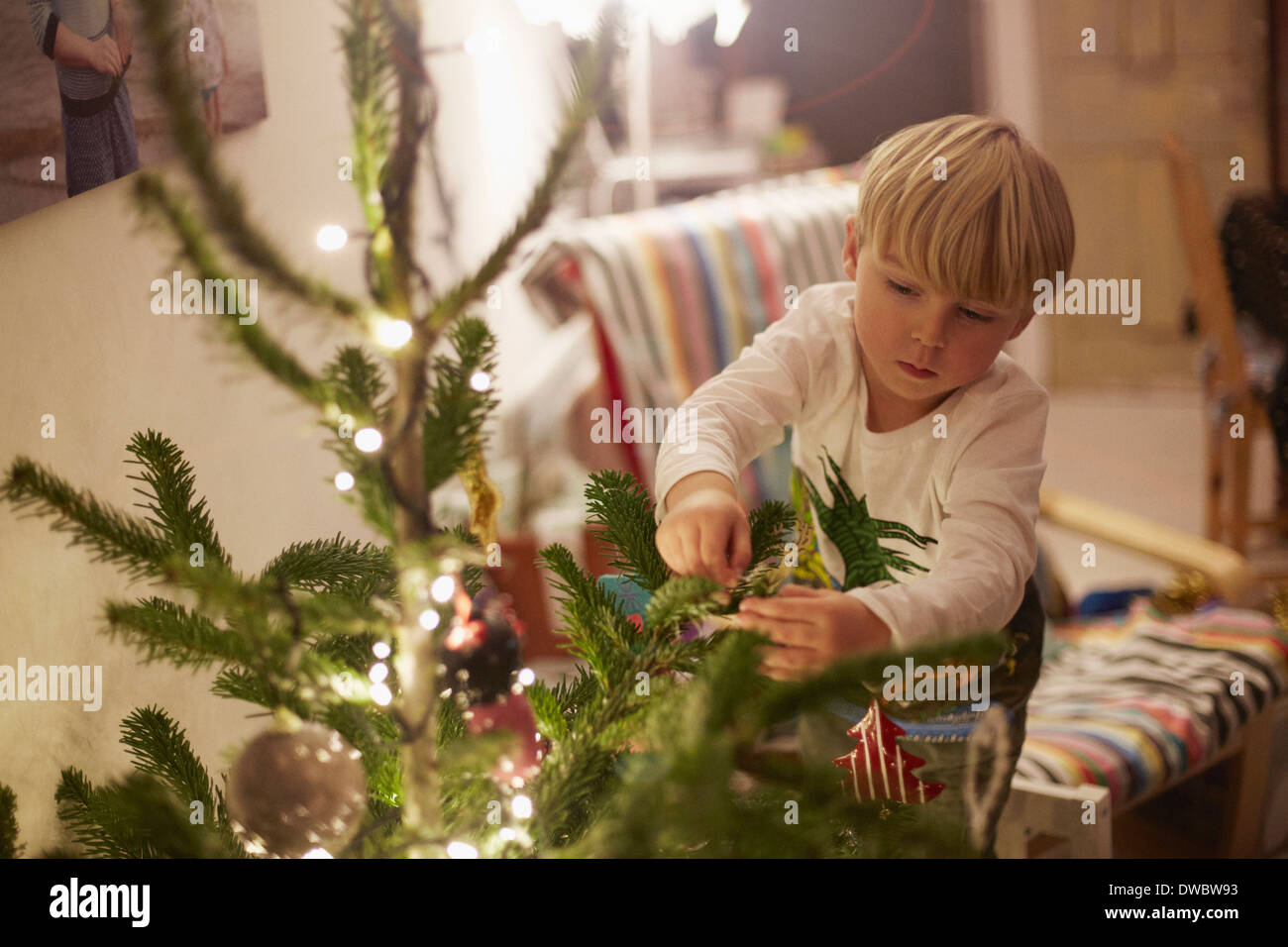 Young boy decorating tree at christmas - Stock Image