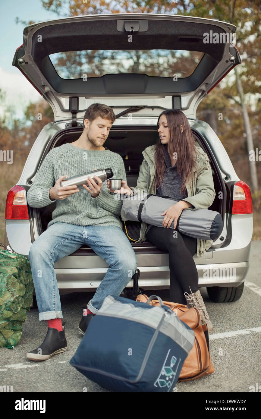 Man pouring coffee for woman while sitting at car trunk during camping - Stock Image