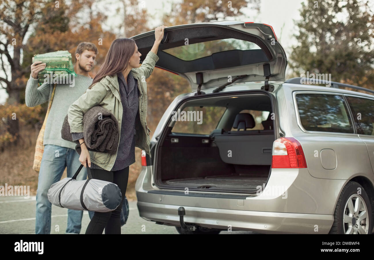 Woman closing car boot while camping with man - Stock Image