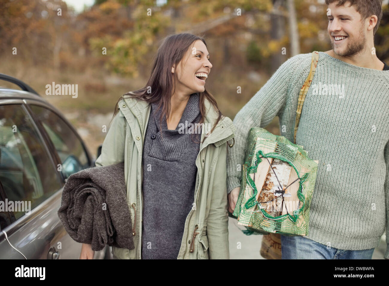 Couple carrying camping equipment by car - Stock Image