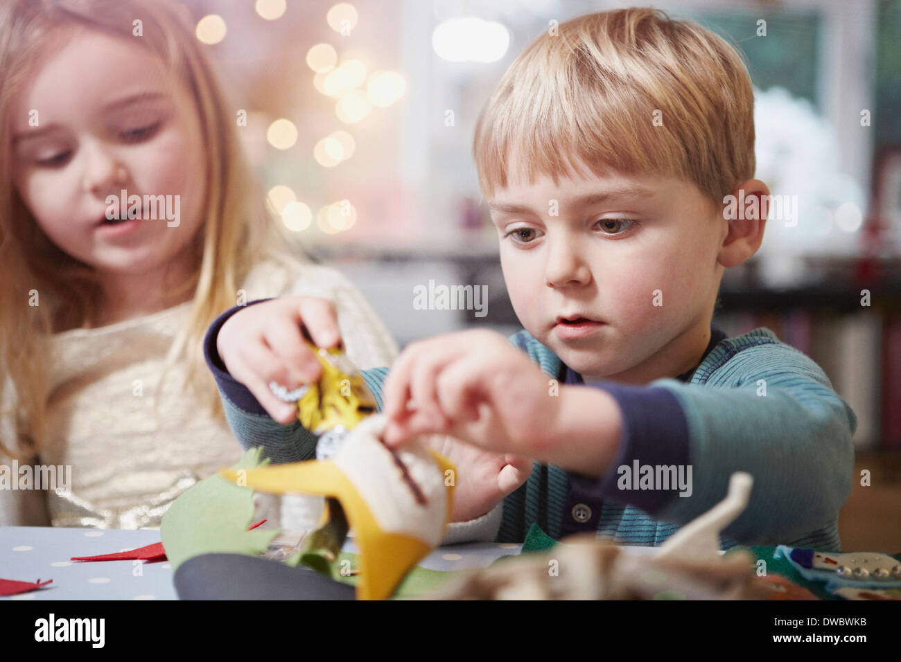 Young brother and sister crafting at kitchen table - Stock Image
