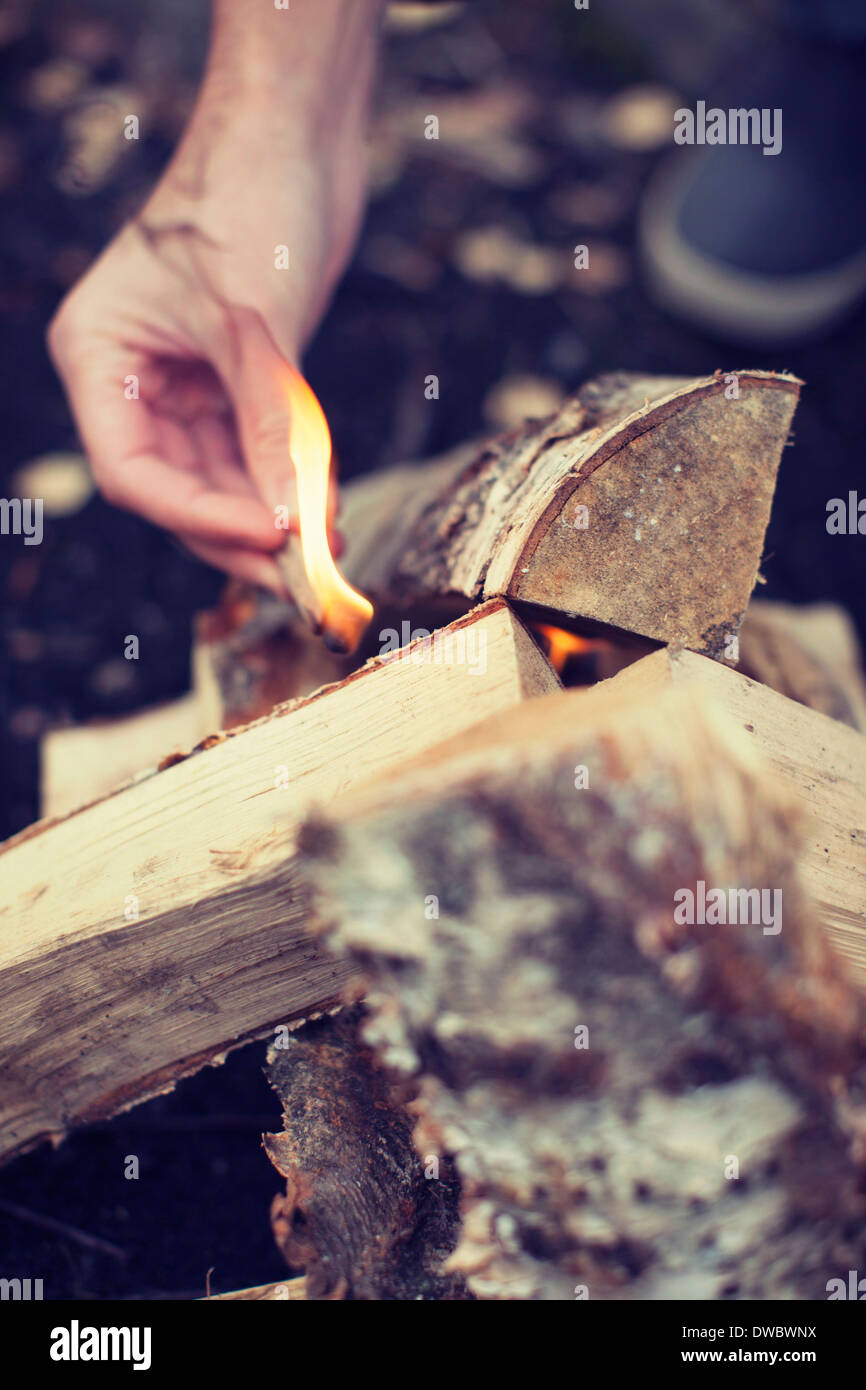 Man's hand igniting bonfire - Stock Image