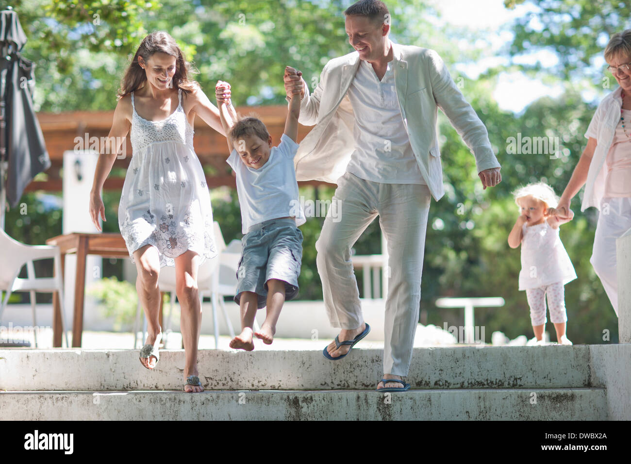 Parents lifting son over steps - Stock Image
