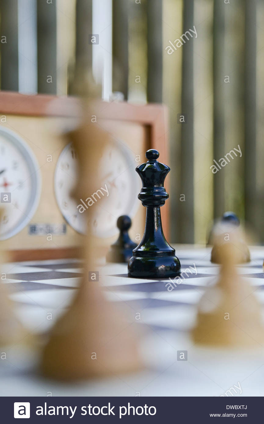 Selective focus of queen facing off king on a chess board - Stock Image