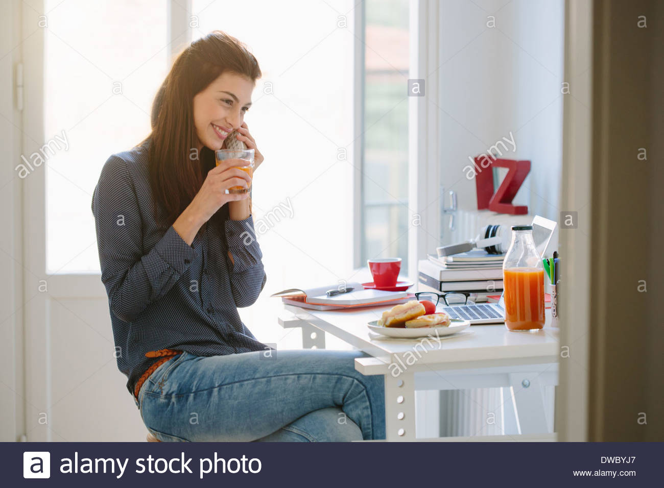 Young woman using telephone while breakfasting - Stock Image