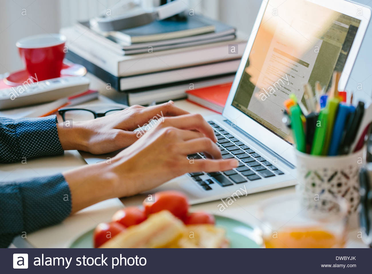 Young woman using laptop while breakfasting - Stock Image