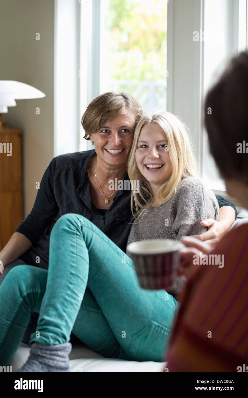 Happy three generation females spending leisure time at home - Stock Image