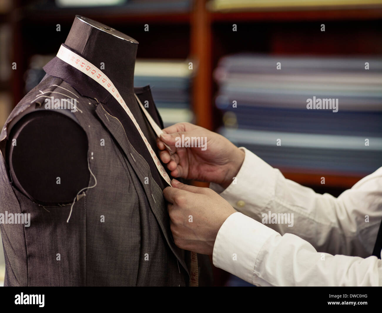 Tailor measuring garment in traditional tailors shop - Stock Image