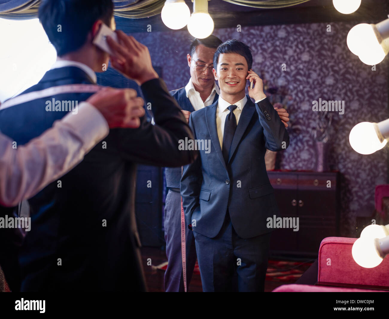 Young man trying on suit in traditional tailors shop - Stock Image