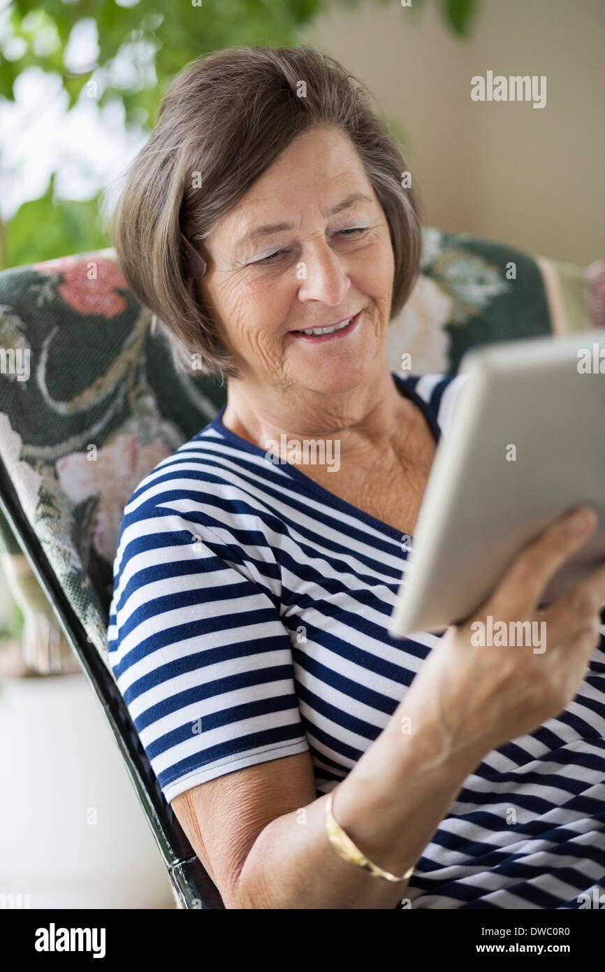 Smiling senior woman using digital tablet at home - Stock Image