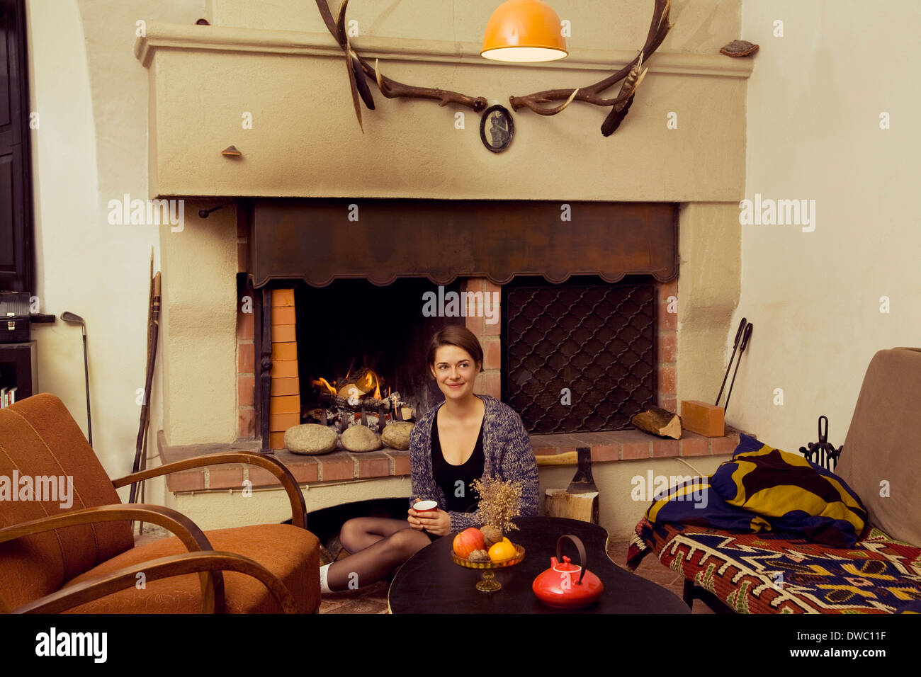 Portrait of young woman sitting on floor next to fireplace Stock Photo