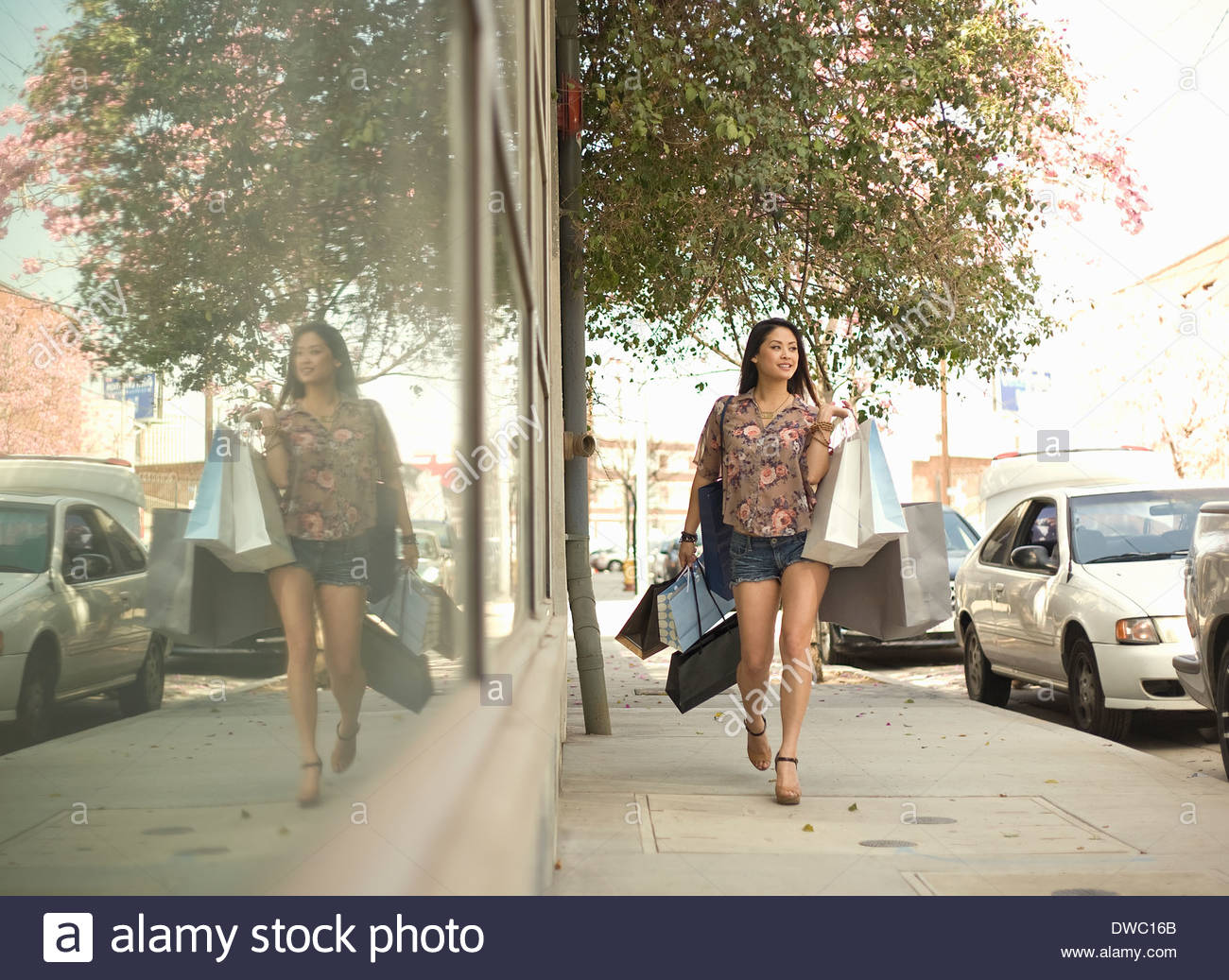 Young woman walking down street with shopping bags Stock Photo