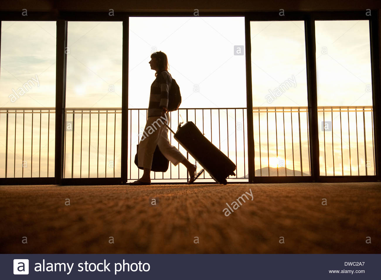 Woman walking through airport with wheeled suitcase - Stock Image